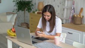 女孩自由职业者在家与膝上型计算机一起使用,在手中采取电话,慢动作 影视素材