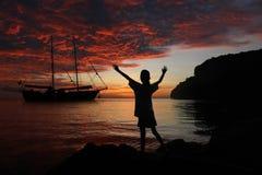 女孩舒展在岩石的有红色天空的胳膊和游艇在 免版税库存照片