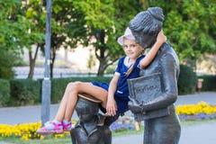女孩舒适地坐纪念碑给第一位老师 免版税图库摄影