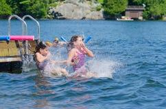 女孩船坞的俯冲轰炸朋友到湖里 免版税库存图片