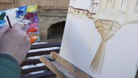 女孩艺术家在老城市街道的手绘画 股票录像