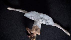 女孩芭蕾舞女演员剪影坐地板,舒展在分裂,芭蕾概念,顶面射击 股票视频