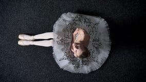 女孩芭蕾舞女演员剪影坐地板,观看在照相机,芭蕾概念,顶面射击 股票录像