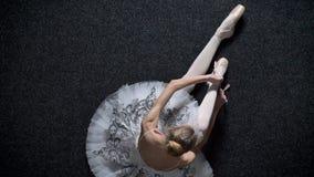 女孩芭蕾舞女演员剪影栓在pointe的丝带,坐地板,芭蕾概念,顶面射击,移动式摄影车射击 股票录像