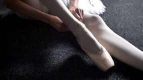 女孩芭蕾舞女演员栓在pointe的丝带,坐地板,芭蕾概念 股票录像