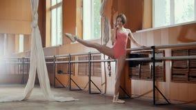 女孩芭蕾舞女演员用途smatphone在跳舞屋子 免版税库存照片