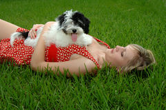 女孩草俏丽的小狗 免版税图库摄影