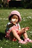 女孩草坐的一点 库存图片