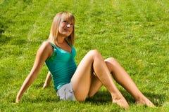 女孩草坐的微笑的年轻人 免版税库存图片