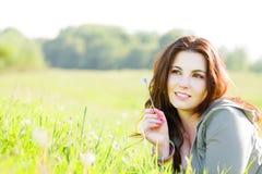 女孩草放松的年轻人 库存照片