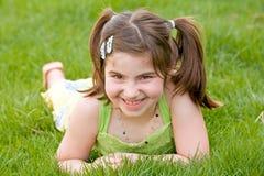 女孩草笑的少许放置 免版税图库摄影
