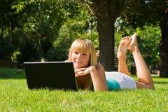 女孩草膝上型计算机年轻人 免版税库存图片