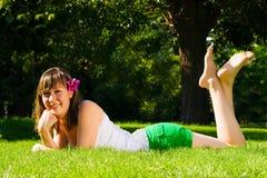 女孩草谎言微笑的年轻人 免版税库存照片
