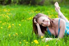 女孩草面带笑容 库存照片