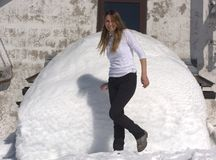 女孩获得与堆的乐趣雪 免版税库存图片