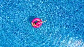 女孩获得乐趣和笑和获得乐趣在一群可膨胀的桃红色火鸟的水池在游泳衣在从abov的夏天 免版税库存图片