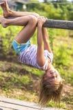 女孩获得乐趣在垂悬颠倒在绿色农村乡下的公园 免版税库存图片