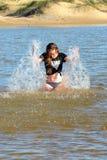 女孩获得乐趣在水中 免版税库存图片