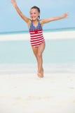 女孩获得乐趣在海滩假日的海 库存照片