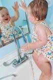 女孩获得乐趣在水槽 库存图片