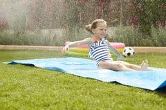 女孩获得在水滑道的乐趣在庭院 免版税库存照片