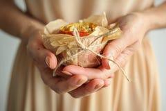 女孩藏品支持与坚果和蜂蜜的苹果在羊皮纸 库存图片