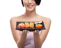 女孩藏品牌照微笑的寿司年轻人 免版税库存图片