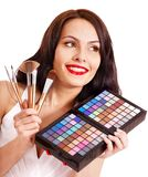 女孩藏品眼影膏和构成画笔。 免版税库存照片