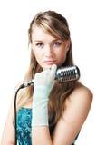 女孩藏品话筒相当减速火箭的年轻人 免版税库存照片