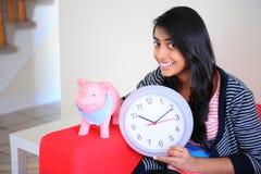 女孩藏品piggybank和时钟 免版税库存照片