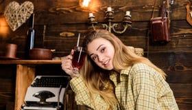 女孩行为似男孩的姑娘放松与玻璃用被仔细考虑的酒在猎场看手人房子里  概念放松 愉快的面孔的夫人在格子花呢披肩衣裳 免版税图库摄影