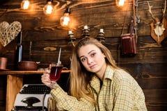 女孩行为似男孩的姑娘放松与玻璃用被仔细考虑的酒在猎场看手人房子里  偶然成套装备的女孩在木葡萄酒坐 免版税库存图片