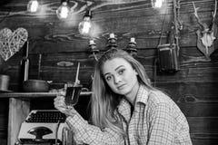女孩行为似男孩的姑娘放松与玻璃用被仔细考虑的酒在猎场看手人房子里  偶然成套装备的女孩在木葡萄酒坐 库存图片