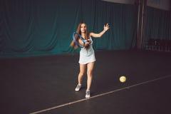 女孩行动的网球员充分的身体画象在室内网球场 库存照片