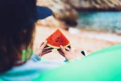 女孩行家在海滩海岸和举行放松在她的手上切片红色新鲜水果西瓜在蓝色海背景,妇女 免版税库存图片