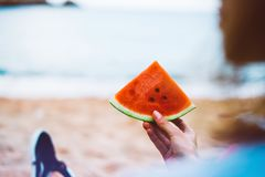 女孩行家在海滩海岸和举行放松在她的手上切片红色新鲜水果西瓜在蓝色海背景 库存照片