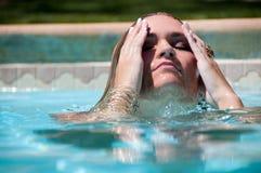 女孩表面化游泳 免版税图库摄影