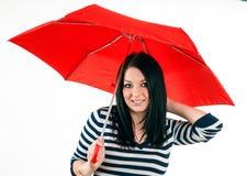 女孩被保护免受与一把红色伞的恶劣天气 库存照片