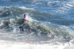 女孩被敲高波浪由海 免版税图库摄影