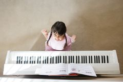女孩被注重弹钢琴 免版税库存照片