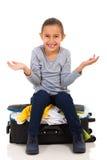 女孩被过度充填的手提箱 库存照片