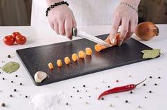女孩裁减红萝卜到在一个黑切板的小切片里 图库摄影