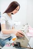 女孩裁缝在缝纫机缝合 免版税图库摄影