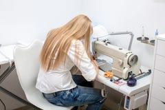 女孩裁缝在缝纫机缝合 免版税库存照片