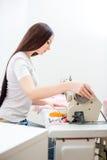 女孩裁缝在缝纫机缝合 图库摄影