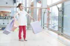女孩装载与纸购物袋 免版税图库摄影