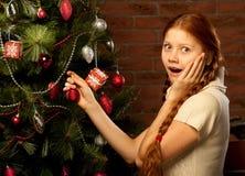 女孩装饰圣诞树 库存图片