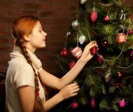 女孩装饰圣诞树 图库摄影