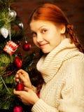 女孩装饰圣诞树 免版税库存照片