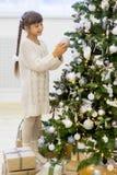 女孩装饰圣诞树 免版税图库摄影